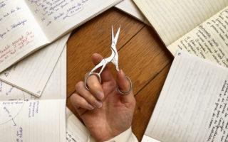 Un cercle de cahiers ouverts avec au centre une main tenant une petite paire de ciseaux